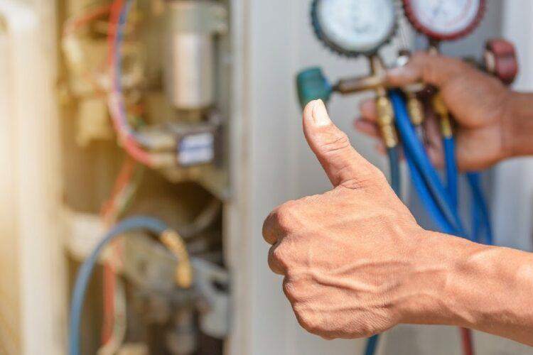 A person giving a thumbs-up while checking an HVAC unit.