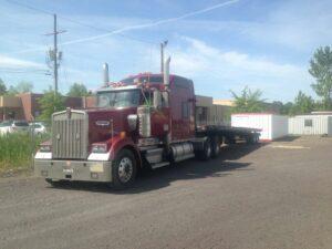 Red semi-truck hauling modular building.