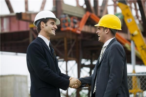 Construction workers shake hands