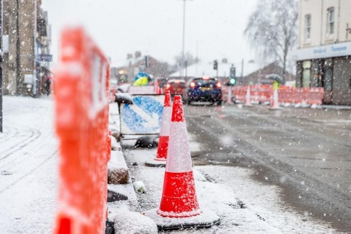 A row of orange traffic cones on a snowy street.