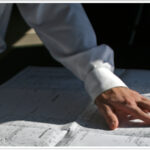 Man uses hand to follow along a design build plan.