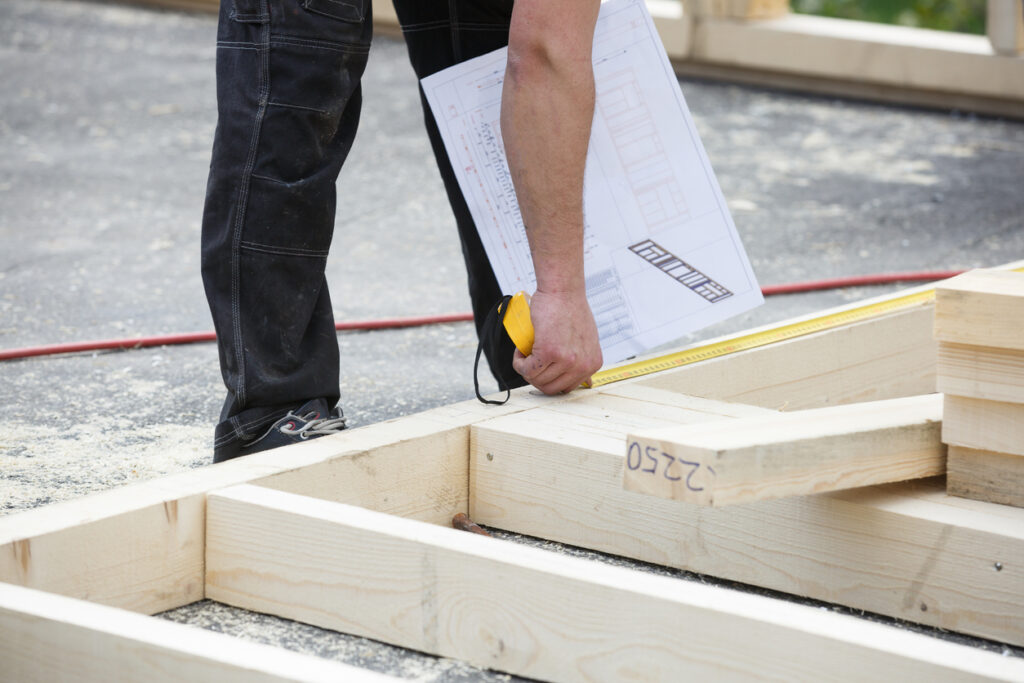 construction worker measuring modular building