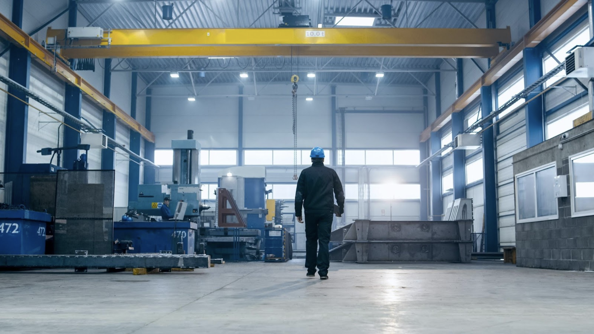 a man in a hardhat walks through an industrial production warehouse