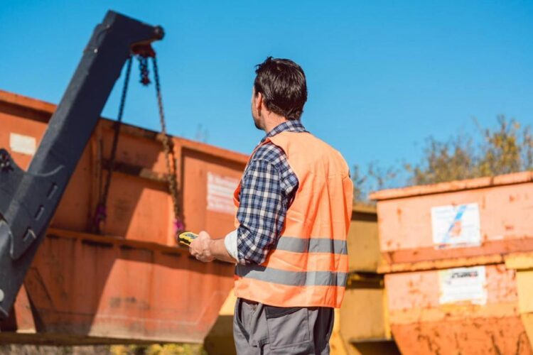 a worker wearing a bright orange vest at a construction site is overseeing equipment