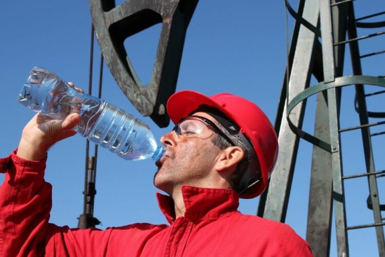 A man wearing a hard hat and glasses drinks from a bottled water.