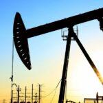 A man in a safety helmet stands near an oil pumpjack.