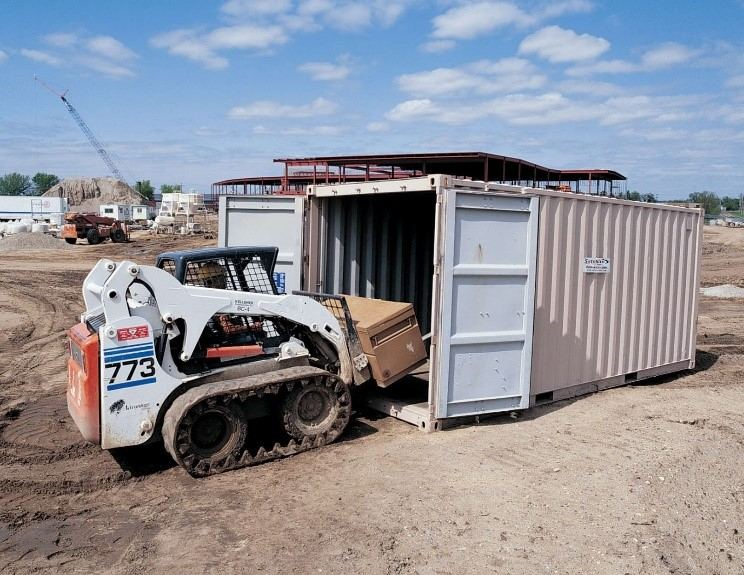 A small front loader placing a box into a storage container.