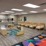 interior of modular educational building infant room with counters, cribs and playmat
