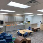 interior of modular educational toddler classroom with cabinets tables and chairs