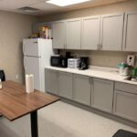 interior of modular educational building teacher lounge with counter table sink and refidgerator