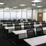 tables and chairs lined up in meeting room