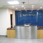 two level reception desk with blue wall and Rolls Royce Logo